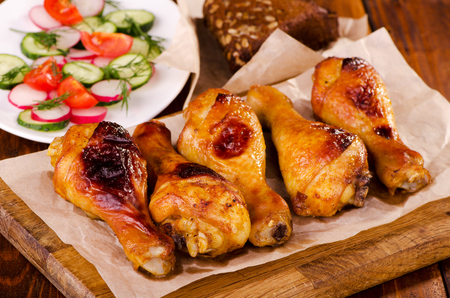 high calorie foods: Chicken legs on a wooden board with fresh vegetable salad Stock Photo
