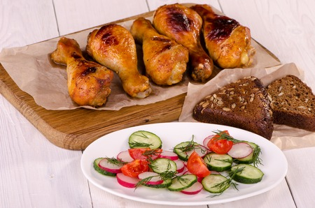 high calorie: Chicken legs on a wooden board with fresh vegetable salad Stock Photo