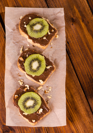 yummy: Sandwiches with chocolate paste, kiwi and walnuts on a wooden background, top view