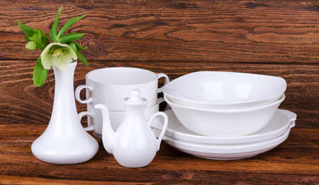 crockery: white crockery - a vase with a flower, soup bowls, and a gravy boat on a wooden background Stock Photo