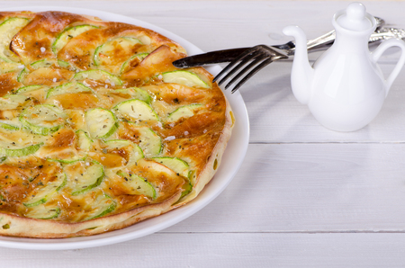 Pie with zucchini on a white wooden table Stock Photo