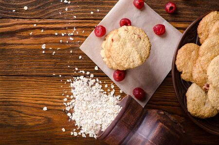 oatmeal: Oatmeal cookies with flakes and cherries on a wooden table. Healthy dessert.
