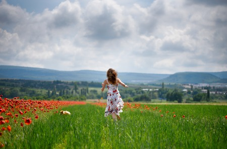 A young girl runs through the meadow to a dog hiding in the grass
