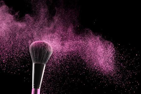 pink blush exploding above a brush on black background 스톡 콘텐츠