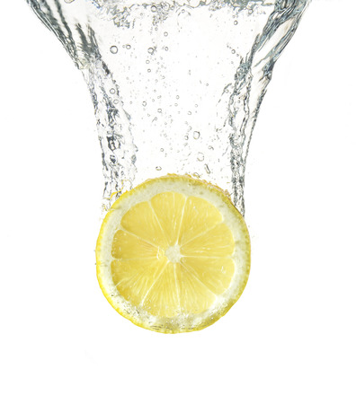 slice of ripe lemon falling into water Stock Photo