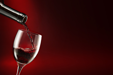 bottle pouring wine in a glass isolated on dark red background