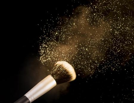 golden glittering blusher explosion isolated on black background