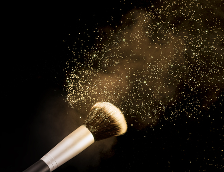 golden glittering blusher explosion isolated on black background