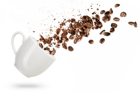 coffee beans spilled out of a cup isolated on white background Foto de archivo