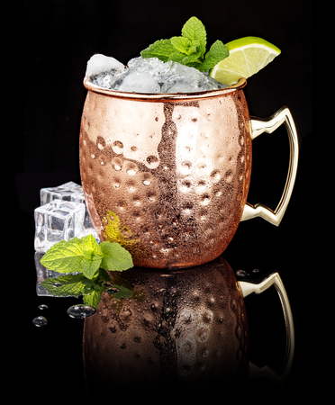 frosty Moscow Mule in a copper cup isolated on black background