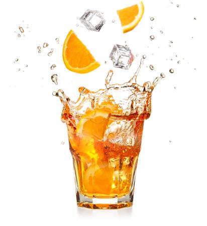 rodajas de naranja y cubitos de hielo cayendo en un cóctel de salpicaduras aislado sobre fondo blanco