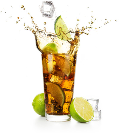 lime slice and ice cube falling into splashing cuba libre cocktail Stock Photo