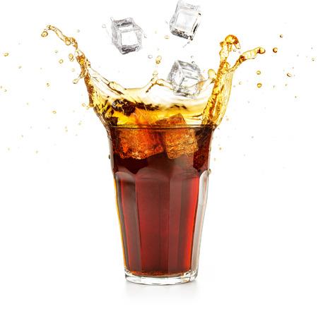 Cubetti di ghiaccio che cadono in una bevanda di cola spruzzi isolato su bianco