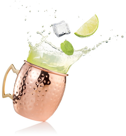 splashing moscow mule cocktail in copper mug on white background 스톡 콘텐츠