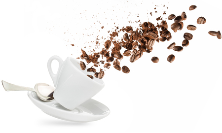 coffee beans and powder spilling out of a cup isolated on white Stockfoto