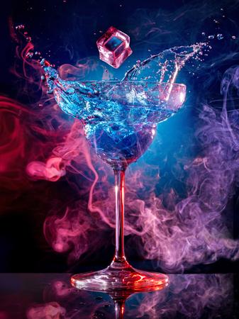 ice cube falling into splashing cocktail on smoky background