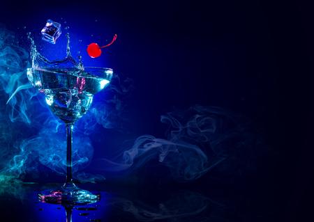 Eis und Kirsche, die in einem Cocktailspritzer auf blauem rauchigem Hintergrund fallen Standard-Bild