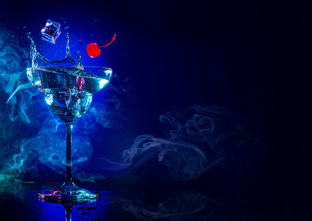 hielo y cereza cayendo en un cóctel splash sobre fondo azul ahumado Foto de archivo