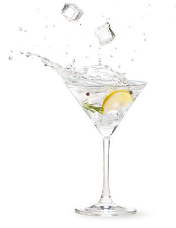 Cubitos de hielo cayendo en un cóctel de gin martini salpicando sobre fondo blanco.