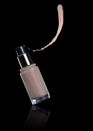liquid foundation sprayed out of a bottle isolated on black background