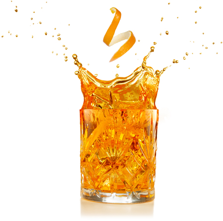 orange zest falling into a splashing cocktail isolated on white