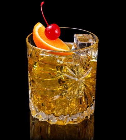 whiskey cocktail garnished with orange and cherry isolated on black