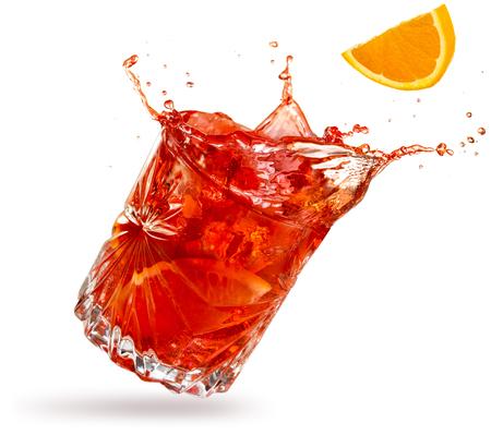 orange slice falling into a splashing negroni tilted on white background Banco de Imagens
