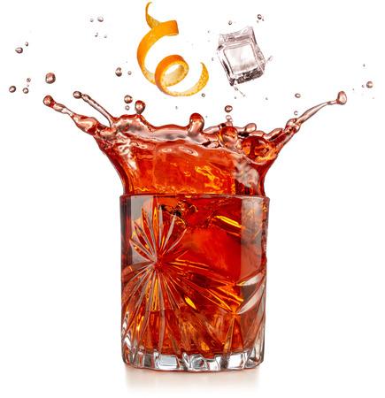 orange zest and ice falling into splashing negroni isolated on white