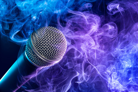 closeup of microphone enveloped in a purple-bluish puff of smoke