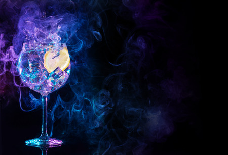 gin tonic cocktail splashing in blue and purple smoky background