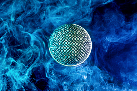 closeup of microphone head in blue smoky background Banco de Imagens