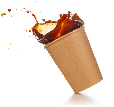 coffee splashing out of a disposable cup tilted on white background