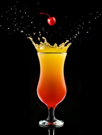 cherry falling into a splashing tequila sunrise isolated on black