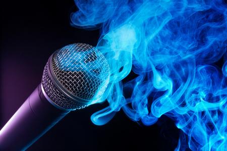 microphone and blue smoke swirls on black background