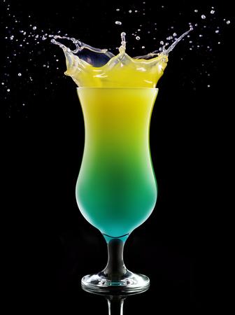 tropical cocktail splashing isolated on black Banco de Imagens