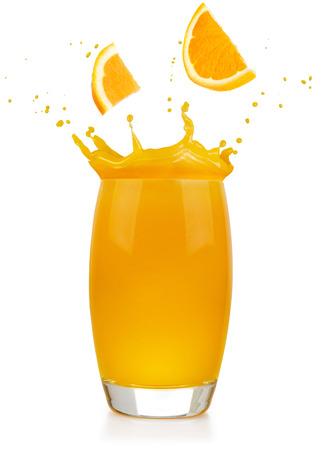 orange slices falling into a splashing juice glass isolated on white Banco de Imagens