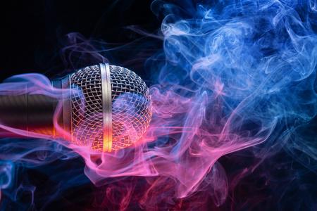 microphone enveloped in multicolored smoke on black gìbackground Banco de Imagens
