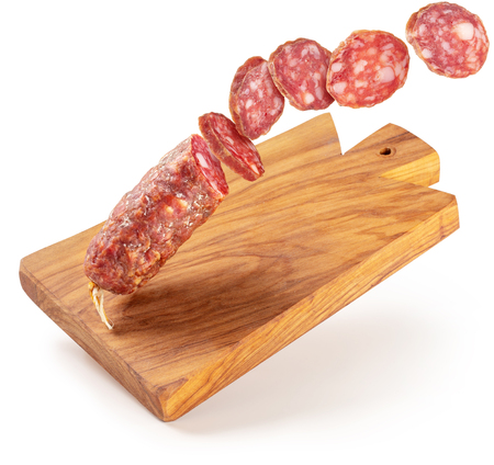 sliced salami flying on a wooden cutting board isolated Banco de Imagens