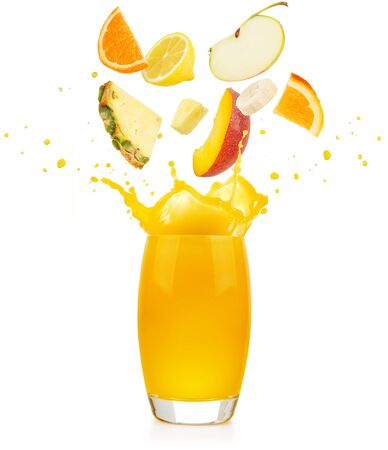 pieces of fruit falling into a yellow juice glass splashing on white background 写真素材 - 129995991