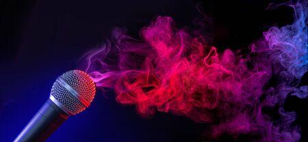 microphone in a purple-bluish smoke on black background