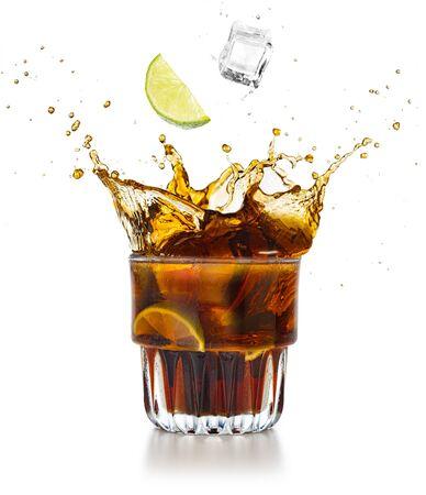 Limettenspalte und Eiswürfel fallen in ein spritzendes Cola-Getränk