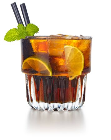 rum and cola drink garnished with lime wedges and mint leaf
