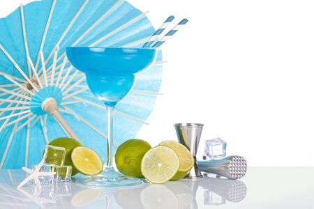 blue margarita cocktail, lime and jigger, umbrella on the background, isolated on white
