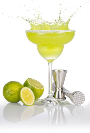 bartender tools and lime fruits around a splashing margarita glass