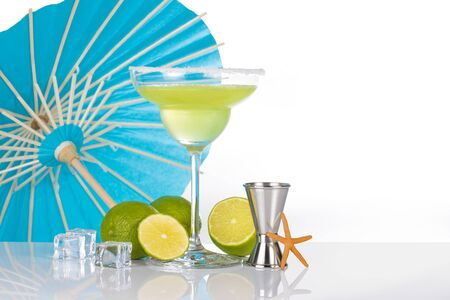 margarita cocktail, lime and jigger, umbrella on the background, isolated on white
