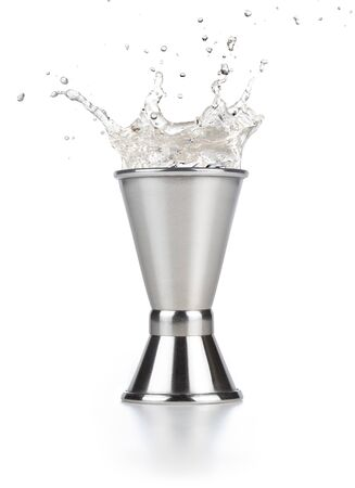 alcohol splashing out of a steel jigger isolated on white 版權商用圖片