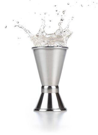 Alkohol spritzt aus einem Stahljigger isoliert auf weiß
