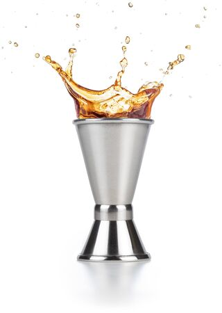 brown liquor splashing out of a jigger isolated on white background