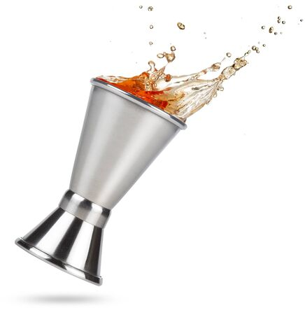 liquor spilling out of a tilted jigger isolated on white background