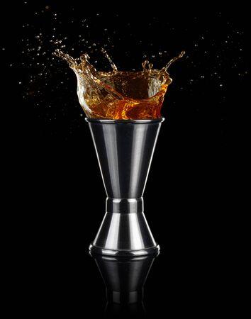 liquor splashing out of a jigger isolated on black background